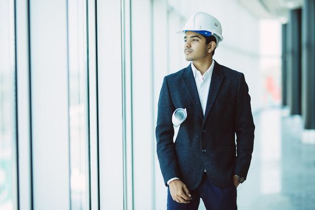 Indiański męski miejsce kontrahenta inżynier trzyma błękitnego druku papierowego odprowadzenie przy budową z ciężkim kapeluszem