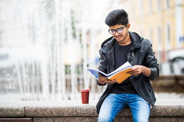 Indiański studencki mężczyzna trzyma stos książki siedzi blisko fontanny na ulicie