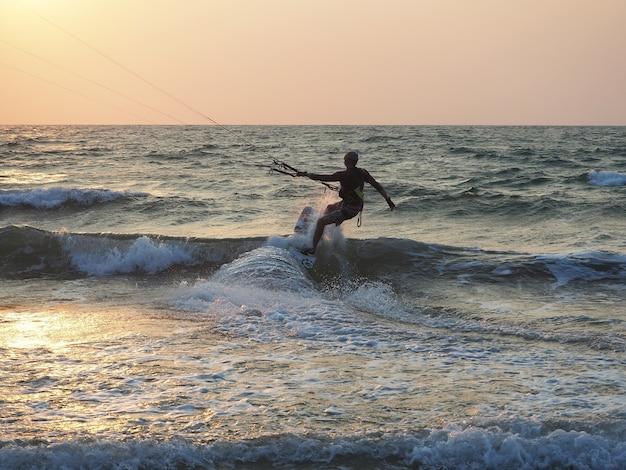 Indie, goa, arambol, człowiek kitesurfingowy blisko wybrzeża o zachodzie słońca
