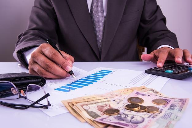 Indie i koncepcja księgowa pokazująca księgowego pracującego nad formularzami podatku dochodowego lub planowaniem budżetu z banknotami walutowymi, kalkulatorem i domem lub samochodem modele 3d