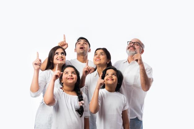 Indn wielopokoleniowa rodzina wskazująca lub prezentująca pustą przestrzeń, stojąca odizolowana od białej ściany