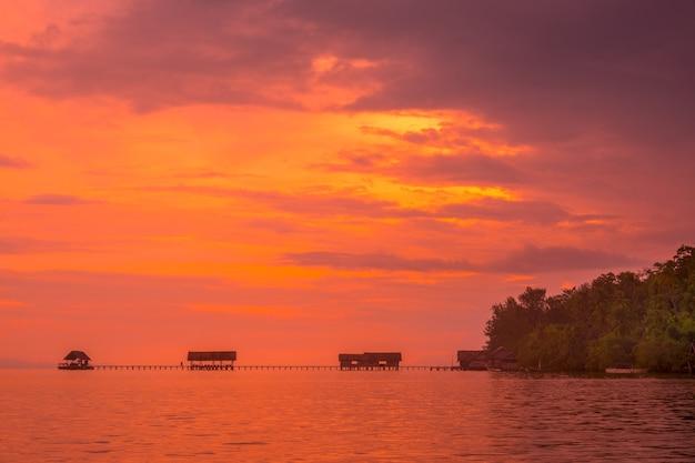 Indonezja. archipelag raja ampat. wybrzeże wyspy z pomostem dla łodzi. spokojny ocean i pomarańczowy zachód słońca