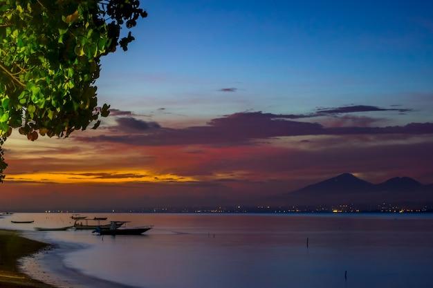 Indonezja. plaża po zachodzie słońca i przywiązane puste łodzie. światła miasta po drugiej stronie zatoki