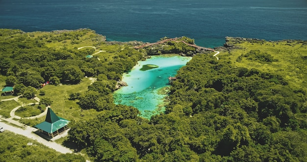 Indonezja punkt orientacyjny jeziora jadeitowego słonej wody weekuri na wyspie sumba. epicki kurort nad przejrzystym jeziorem z naturalną różnorodnością. niesamowita atrakcja architektoniczna z drogą i samochodami wśród zielonych roślin tropikalnych, drzew