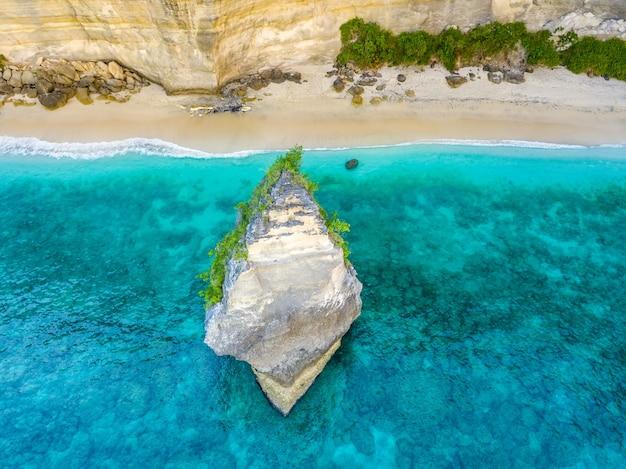 Indonezja. pusta plaża w pobliżu klifu na wyspie penida. ostra skała blisko brzegu. widok z lotu ptaka