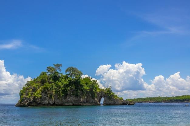 Indonezja. skalista wyspa z lasem, słonecznym niebieskim niebem i pięknymi chmurami