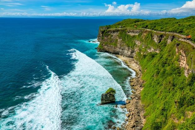 Indonezja. słoneczna pogoda nad oceanem i chmury na horyzoncie. ścieżka wzdłuż szczytu skalistego tropikalnego brzegu. arbours na odpoczynek
