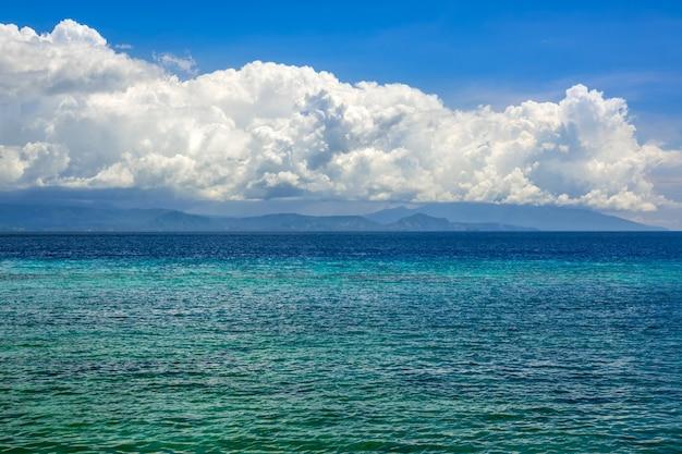 Indonezja. słoneczny dzień. turkusowa woda spokojnego oceanu. zaskakująco piękne chmury nad odległą wyspą