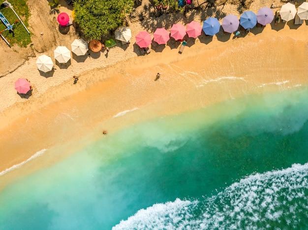 Indonezja. tropikalna piaszczysta plaża przy słonecznej pogodzie. turkusowa woda i parasole plażowe. widok z lotu ptaka
