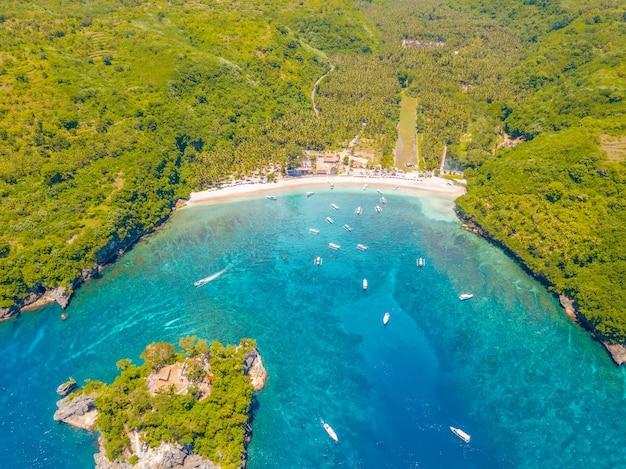 Indonezja. tropikalna zatoka przy słonecznej pogodzie. ośrodek turystyczny w dżungli. plaża i autentyczne łodzie. widok z lotu ptaka