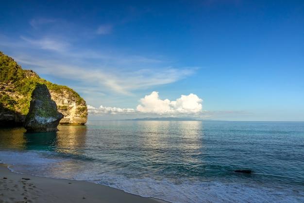 Indonezja. wieczór na pustej, zacienionej plaży na tropikalnej wyspie. błękitne niebo i jasne chmury oświetlone przez słońce nad odległą wyspą na oceanie