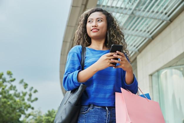 Indonezyjska kobieta z papierowymi torbami używać smartphone
