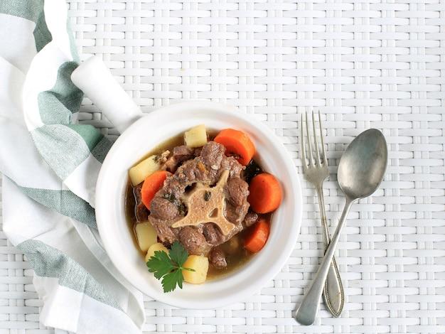 Indonezyjska zupa ogonowa lub buntut sop na białej misce, odizolowane