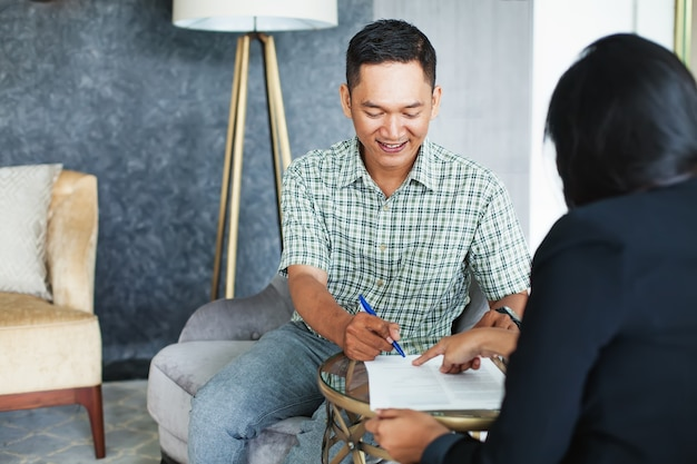 Indonezyjski mężczyzna podpisujący umowę na spotkaniu