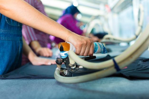 Indonezyjski pracownik z płaskim żelazem w fabryce włókienniczej