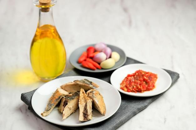 Indonezyjskie jedzenie: przygotowanie składników pampis tongkol suwir. surowy tuńczyk z makreli (pindang tongkol) na białym talerzu z olejem, pastą chili, czosnkiem i szalotką.