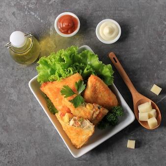 Indonezyjskie przekąski: smażone risole lub warzywa risol z mięsem mielony. podawane z sosem chili i majonezem, udekorowane świeżą pietruszką.