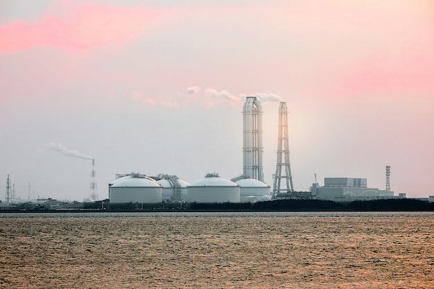Industrial estate area lub factory z dymem i morzem w czasie zachodu słońca, przemysł i koncepcja środowiska.