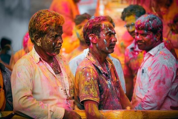 Indyjscy mężczyźni cieszący się festiwalem holi z kolorami w tłumie