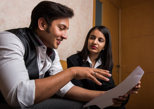 Indyjscy młodzi ludzie biznesu lub prawnicy konsultujący się lub dyskutujący, trzymając w ręku papier lub dokumenty