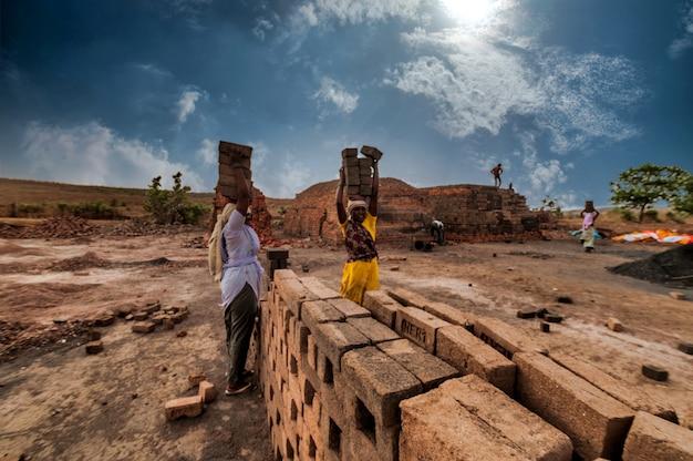 Indyjscy robotnicy niosący cegły na głowach do pieca w fabryce.