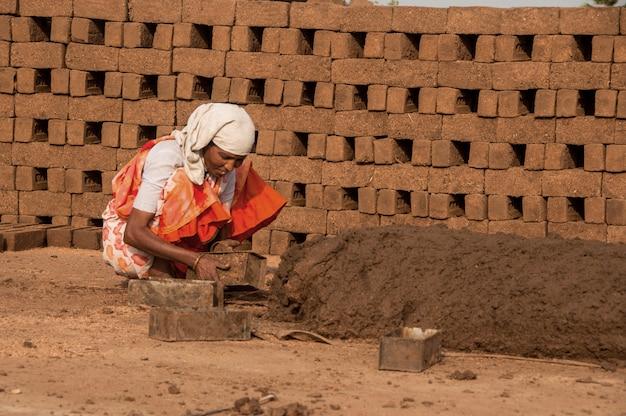 Indyjscy robotnicy przetwarzają na glinie lub błocie i wyrabiają ręcznie tradycyjne cegły w cegielni, fabryce lub na polu.