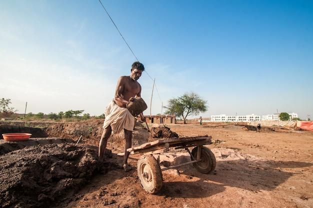 Indyjscy robotnicy przetwarzający i niosący glinę w cegielni