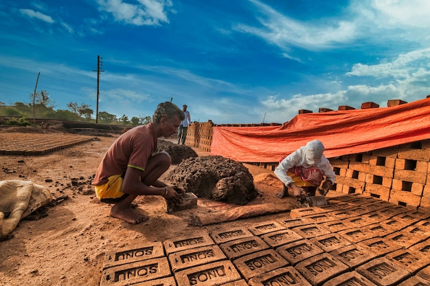Indyjscy robotnicy ręcznie wyrabiający cegły z gliny w fabryce lub na polu.