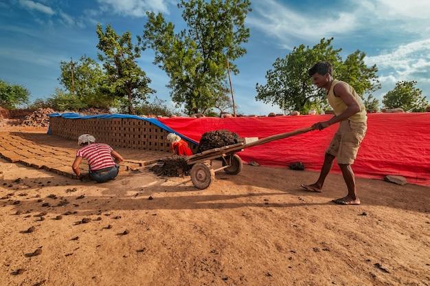 Indyjscy robotnicy ręcznie wytwarzający w fabryce surowiec do wyrobu glinianych cegieł.