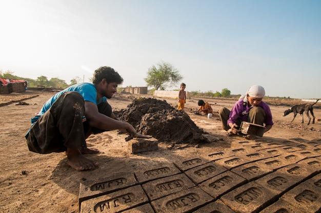 Indyjscy robotnicy wykonujący ręcznie tradycyjne cegły w cegielni