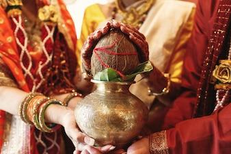 Indyjscy rodzice panny młodej trzymają miskę z kokosem pod jej rękami