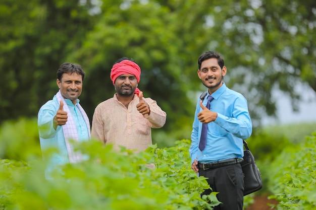 Indyjscy rolnicy pokazujący aprobaty z bankierem lub agronomem na polu rolniczym.
