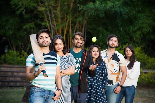 Indyjska azjatycka kolegium młodzi przyjaciele pozują z kijem do krykieta i piłką rzucając wyzwanie lub pozują do zdjęcia