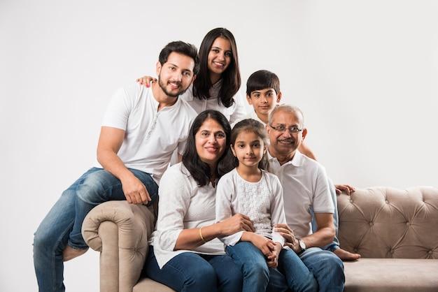 Indyjska azjatycka rodzina siedzi na kanapie lub kanapie na białym tle