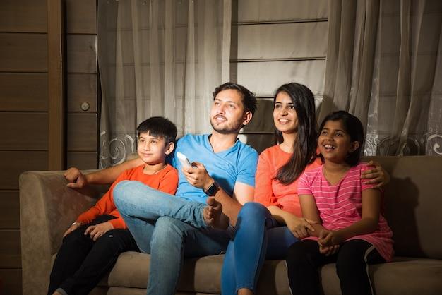 Indyjska azjatycka rodzina składająca się z czterech osób ogląda telewizję lub telewizję siedząc na kanapie lub kanapie