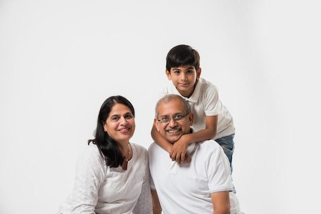 Indyjska azjatycka starsza para lub dziadek i babcia z wnukiem, wyizolowani nad białymi