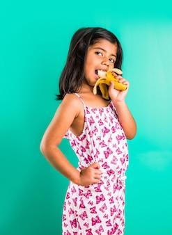 Indyjska dziewczyna je banana, stojąc na białym tle nad zielonym tłem