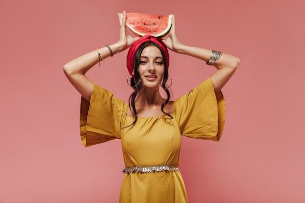 Indyjska dziewczyna z czarnymi falującymi włosami w opasce i żółtym modnym ubraniu trzymająca arbuza na głowie na różowej ścianie