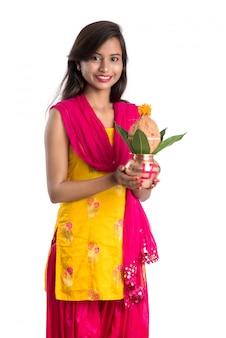 Indyjska dziewczynka trzymająca tradycyjną miedzianą kalashę, festiwal indyjski, miedzianą kalash z liściem kokosa i mango z kwiatową dekoracją, niezbędna w hinduskiej pooja.