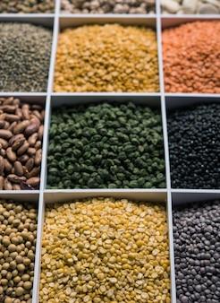 Indyjska fasola, rośliny strączkowe, soczewica, ryż i ziarno pszenicy w białym drewnianym pudełku z komórkami, selektywne focus.