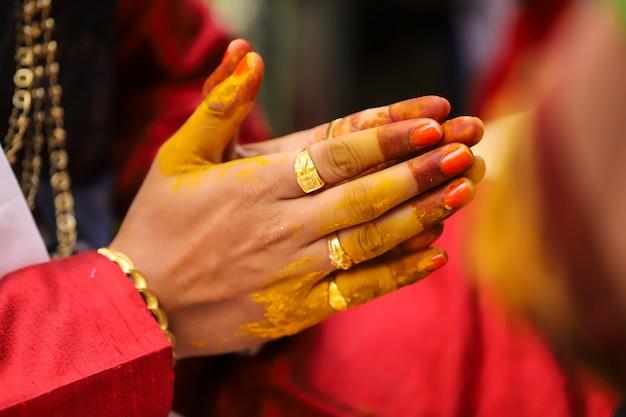 Indyjska fotografia ślubna, ręce pana młodego ceremonii haldi