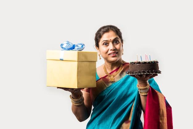 Indyjska inteligentna starsza pani świętująca urodziny sama z ciastem, mając na sobie designerską sari i biżuterię