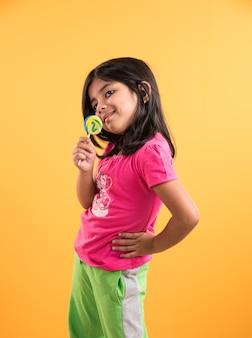 Indyjska mała dziewczynka z lolipopem lub loly popem, azjatycka dziewczyna i lolipopem lub lolypopem, figlarna indyjska urocza dziewczyna pozuje z lolipopem lub cukierkiem