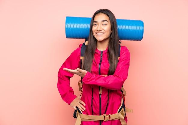Indyjska młoda alpinistka z dużym plecakiem na różowym tle, wyciągając ręce na bok za zaproszenie