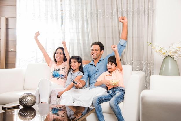 Indyjska młoda azjatycka rodzina oglądająca telewizję razem siedząc na kanapie, selektywne skupienie