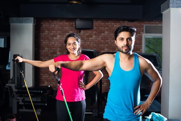 Indyjska młoda para azjatycka ćwicząca z zespołem oporowym na siłowni
