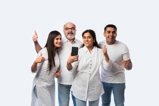 Indyjska młoda para z rodzicami używającymi lub trzymającymi smartfona ze szczęśliwymi wyrazami twarzy, stojąca na tle bieli