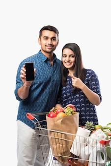 Indyjska młoda para z wózkiem na zakupy lub wózkiem pełnym artykułów spożywczych, warzyw i owoców. izolowane zdjęcie pełnej długości na białej ścianie