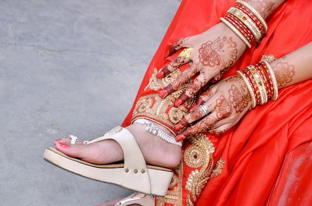 Indyjska panna młoda pokazuje swoje obuwie, payal i mehandi w dniu ślubu