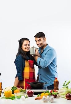 Indyjska para w kuchni - młoda piękna azjatycka żona ciesząca się gotowaniem z mężem z dużą ilością świeżych warzyw i owoców